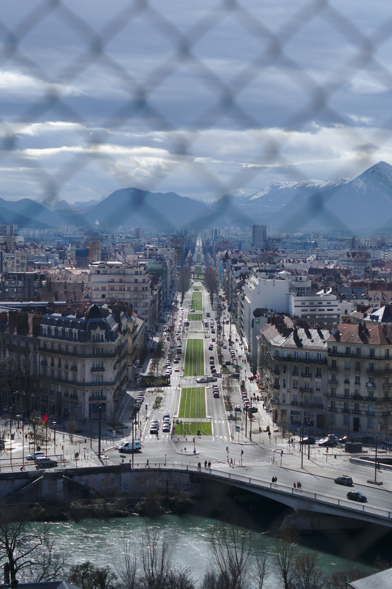 A vertical of Grenoble with a wire fence in the foreground.