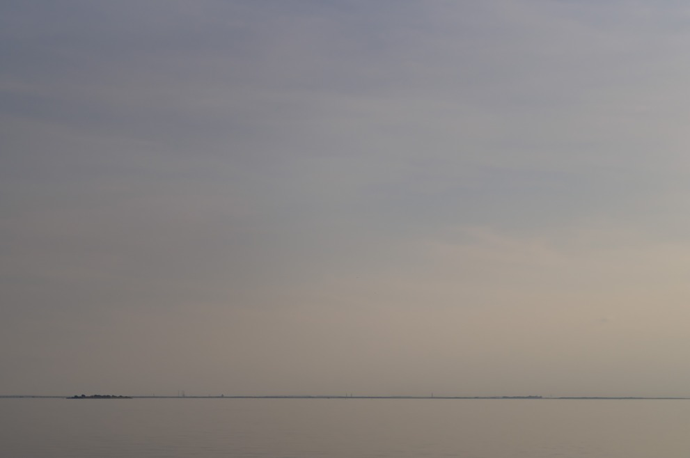 A minimalistic coast line with indistinguishable water and sky.